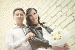 Ungewöhnliche Hochzeitspaare nahe einer Backsteinmauer Lizenzfreie Stockfotos