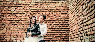 Ungewöhnliche Hochzeitspaare nahe einer Backsteinmauer Stockfoto