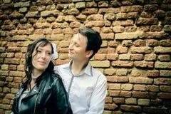 Ungewöhnliche Hochzeitspaare nahe einer Backsteinmauer Lizenzfreie Stockfotografie