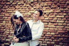 Ungewöhnliche Hochzeitspaare nahe einer Backsteinmauer Stockbilder