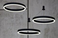 Ungewöhnliche Lichtquellen hängen am Hintergrund einer Marmorwand Lampen in Form eines leuchtenden Ringes Stockbild