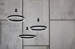 Ungewöhnliche Lichtquellen hängen am Hintergrund einer Marmorwand Lampen in Form eines leuchtenden Ringes Lizenzfreie Stockfotos