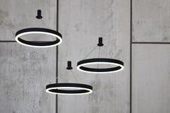 Ungewöhnliche Lichtquellen hängen am Hintergrund einer Marmorwand Lampen in Form eines leuchtenden Ringes Lizenzfreies Stockfoto