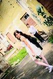 Ungewöhnliche liebevolle Hochzeitspaare an geworfenem Haus Stockbild