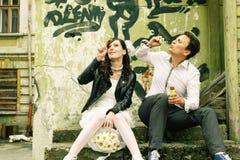 Ungewöhnliche liebevolle Hochzeitspaare nähern sich Wand mit Graffiti geworfenem hou Stockbilder