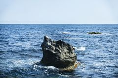 Ungewöhnlicher Stein im Meer Stockbilder