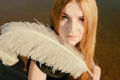 Ungewöhnliches gotisches Mädchen mit dem langem rotem Haar und Feder Lizenzfreie Stockfotografie