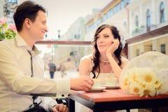 Ungewöhnliches liebevolles Hochzeitspaar im Café trinkt Cappuccino Lizenzfreie Stockbilder