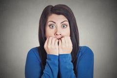 Ungewisse zögernde nervöse Frau, die ihr Fingernagelsehnen besorgt beißt lizenzfreies stockfoto