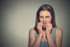 Ungewisse zögernde nervöse Frau, die ihre Fingernägel beißt lizenzfreies stockfoto