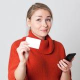 Ungewisses junges blondes Frauenkaufen am Handy mit Kreditkarte Stockfotografie