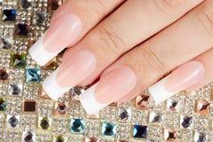 Unghie con il manicure francese artificiale lungo sul fondo variopinto dei cristalli Fotografia Stock