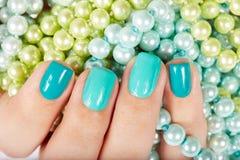Unghie con il manicure sul fondo colorato delle perle Fotografie Stock