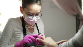 Unghie di lucidatura dello specialista del manicure al cliente Chiodi d'archivio dell'estetista del chiodo alla donna nel salone  archivi video