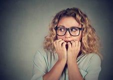 Unghie mordaci sollecitate nervose della giovane donna che guardano ansiosamente Immagini Stock Libere da Diritti