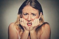 Unghie mordaci sollecitate nervose della giovane donna che guardano ansiosamente aventi bisogno Immagini Stock Libere da Diritti