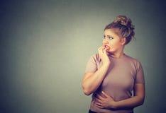 Unghie mordaci sollecitate nervose della giovane donna interessata che guardano ansiosamente Fotografia Stock