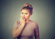 Unghie mordaci sollecitate nervose dello studente della giovane donna che guardano ansiosamente aventi bisogno Fotografia Stock Libera da Diritti