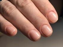 Unghie nude con il manicure a macchina ed i chiarori Immagine Stock