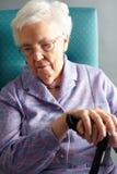 Unglückliche ältere Frau, die im Stuhl sitzt Stockfotografie