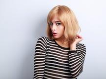 Unglückliche überraschende blonde Frau mit der Kurzhaarfrisur, die mit schaut Stockfoto