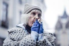 Unglückliche arme Greisin, die sehr kalt sich fühlt lizenzfreies stockbild