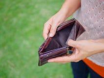 Unglückliche bankrotte Frau mit leerer Geldbörse Stockfoto