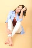 Unglückliche besorgte attraktive schöne junge Frau, die auf dem Boden sitzt Lizenzfreies Stockfoto