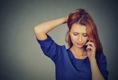Unglückliche besorgte Frau, die an einem Telefon spricht lizenzfreie stockfotos