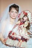 Unglückliche Braut, die eine schöne Puppe anhält Stockfotos