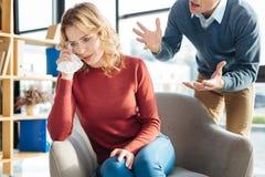 Unglückliche düstere Frau, die auf ihren Ehemann hört Stockbilder