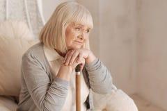 Unglückliche deprimierte Frau, die auf ihrem Spazierstock sich lehnt Stockbild