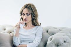 Unglückliche deprimierte Frau, die ein Papiergewebe hält Lizenzfreie Stockbilder
