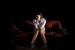 Unglückliche einsame deprimierte Frau, die auf alter Couch und contempl sitzt Lizenzfreies Stockbild