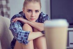 Unglückliche einsame deprimierte Jugendliche zu Hause, sitzt sie auf der Couch und ihrem Kopf mit seinen Füßen gestützt Stockfotografie