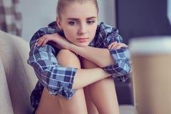 Unglückliche einsame deprimierte Jugendliche zu Hause, sitzt sie auf der Couch und ihrem Kopf mit seinen Füßen gestützt Lizenzfreie Stockfotos