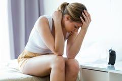 Unglückliche einsame deprimierte junge Frau, die zu Hause auf Bett sitzt Krisenkonzept Lizenzfreie Stockbilder