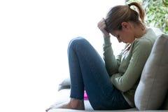 Unglückliche einsame deprimierte junge Frau, die zu Hause auf Sofa sitzt Krisenkonzept Lizenzfreies Stockbild