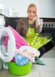 Unglückliche Frau, die Waschmaschine verwendet Stockfotografie