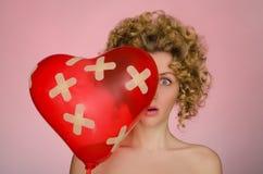 Unglückliche Frau mit Ball in Form des Herzens Lizenzfreies Stockfoto
