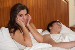 Unglückliche Frau und ihr schnarchender Ehemann. Stockfotografie