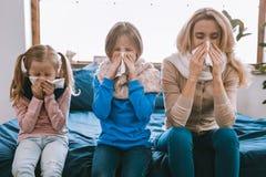 Unglückliche freudlose niesende Familie stockbilder