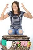 Unglückliche frustrierte attraktive junge Frau, die auf einem überfließenden Koffer knit stockfotos