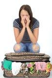 Unglückliche frustrierte attraktive junge Frau, die auf einem überfließenden Koffer sitzt stockfoto