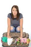 Unglückliche frustrierte attraktive junge Frau, die auf einem übergelaufenen Koffer sitzt lizenzfreies stockfoto