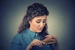 Unglückliche frustrierte junge Frau überraschte sie ist verlierendes Haar, bemerkte aufgeteilte Enden Lizenzfreies Stockfoto