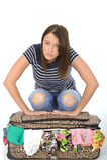 Unglückliche frustrierte junge Frau, die an über verpacktem Koffer sich lehnt stockbilder