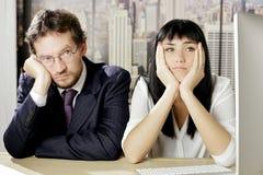 Unglückliche Geschäftsleute, die auf dem Schreibtisch niedergedrückt sitzen lizenzfreie stockfotografie
