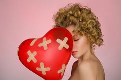 Unglückliche junge Frau mit Ball in Form des Herzens Stockfotos