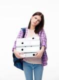 Unglückliche junge Frau mit Rucksack und Ordnern Lizenzfreie Stockbilder